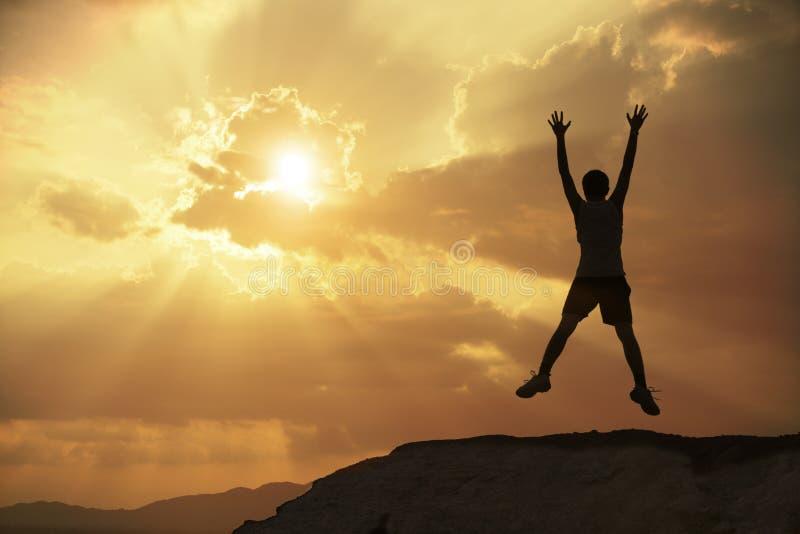 Uomo della siluetta che salta con il tramonto o l'alba fotografie stock libere da diritti