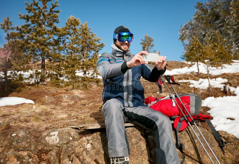 Uomo della viandante che prende il paesaggio della montagna delle fotografie con il fon mobile fotografia stock libera da diritti