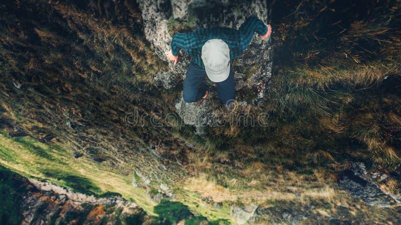 Uomo della viandante che si siede sul concetto di vacanze di avventura di stile di vita di viaggio di vista aerea di Cliff Bridge fotografie stock libere da diritti