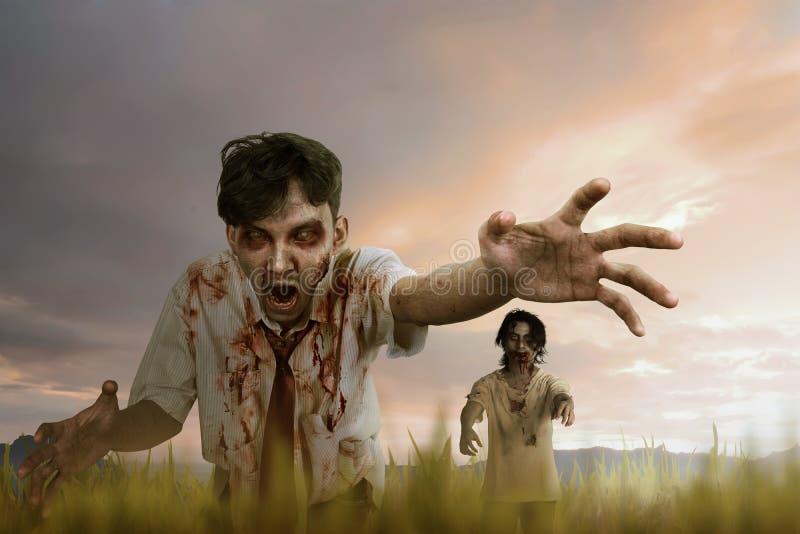 Uomo dello zombie di due asiatici con il fronte pazzo e la condizione sporca della mano fotografie stock