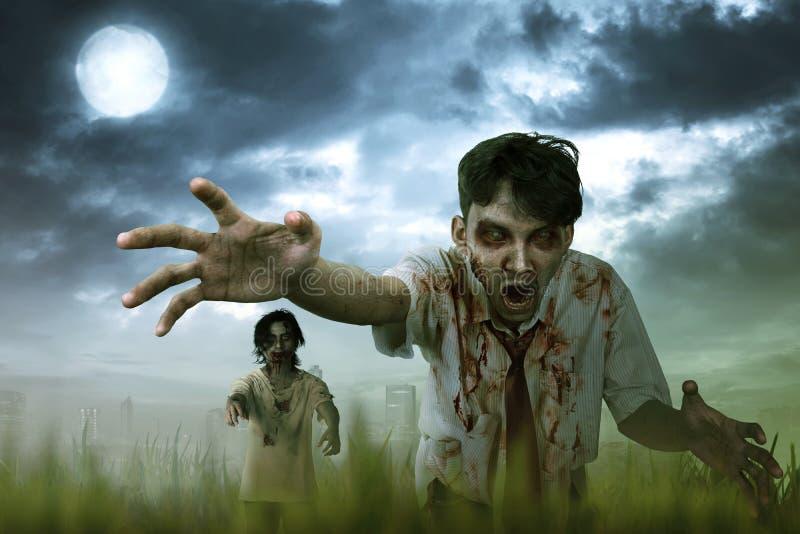 Uomo dello zombie di due asiatici con sangue e la condizione sporca della mano fotografia stock libera da diritti