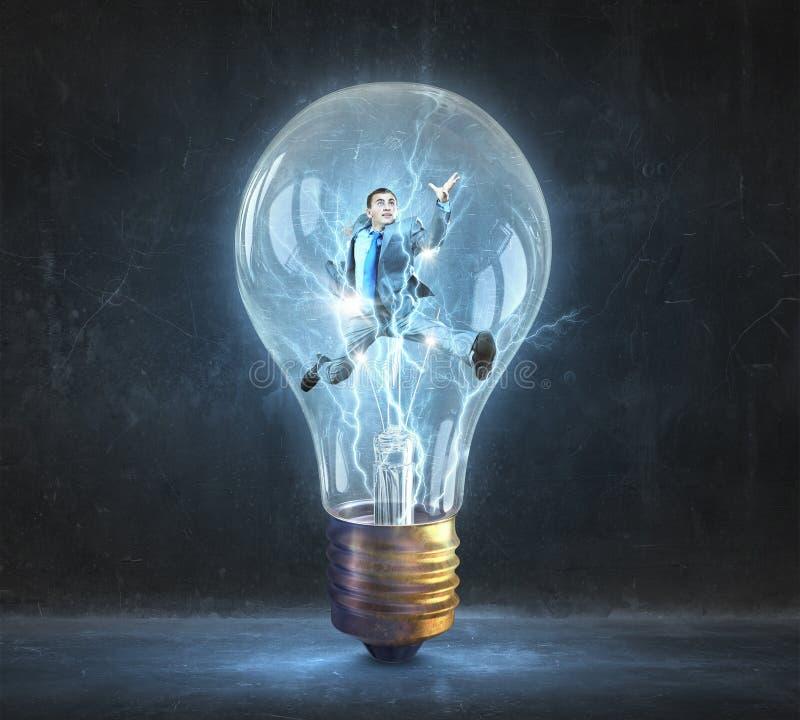 Uomo dentro della lampadina elettrica immagini stock