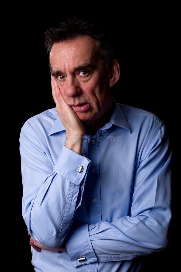 Uomo depresso ansioso triste di affari con la mano a Chin fotografia stock libera da diritti