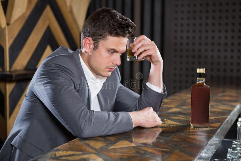 Uomo depresso che mangia vetro di whiskey al contatore immagine stock