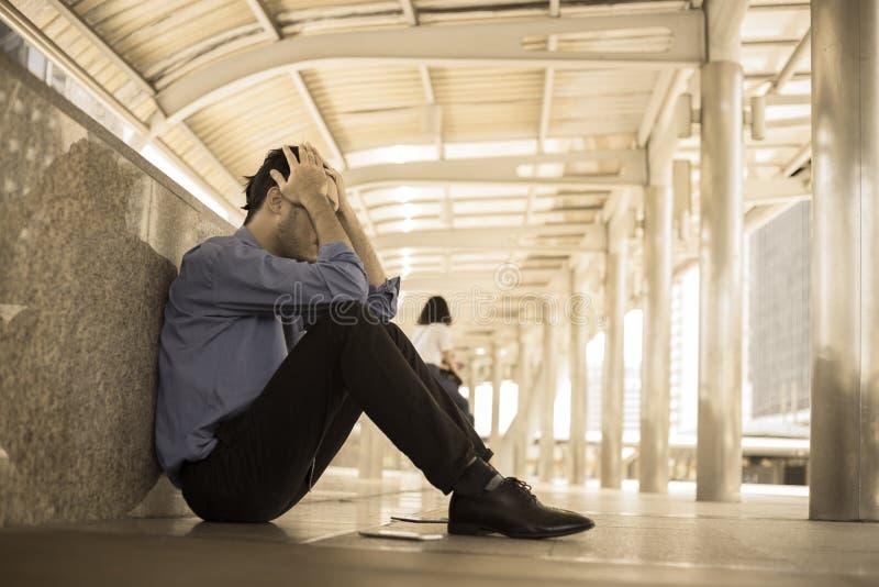 Uomo depresso che si siede sulla testa del pavimento in mani immagini stock