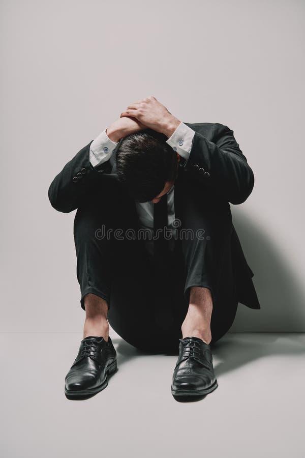 Uomo depresso di affari che si siede sulla testa del pavimento in mani su fondo bianco fotografia stock