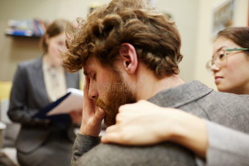 Uomo depresso nel consiglio della sessione fotografia stock libera da diritti