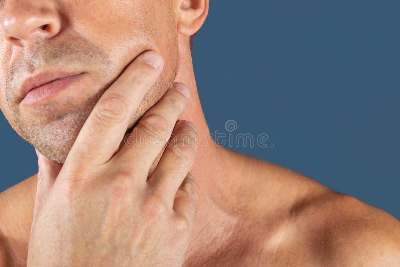 uomo depresso triste nel dolore che tiene la sua guancia Ritratto di un uomo su fondo blu Espressione facciale di emozione sensib fotografia stock