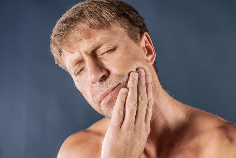 uomo depresso triste nel dolore che tiene la sua guancia Ritratto di un uomo su fondo blu Espressione facciale di emozione sensib immagine stock libera da diritti