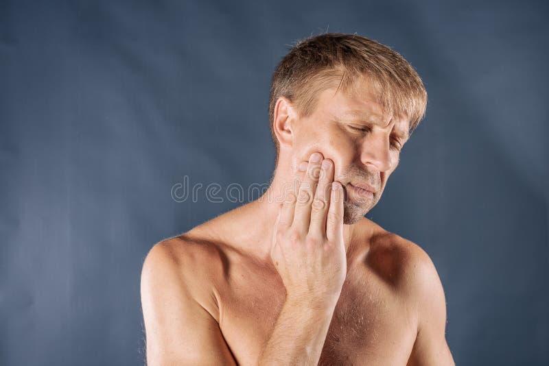 uomo depresso triste nel dolore che tiene la sua guancia Ritratto di un uomo su fondo blu Espressione facciale di emozione sensib fotografie stock libere da diritti