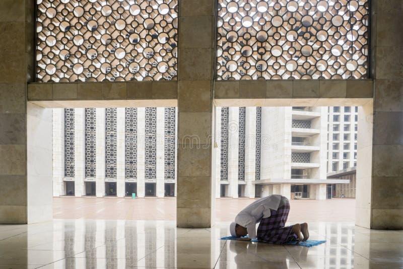 Uomo devoto che fa Salat sulla moschea di Istiqlal fotografia stock libera da diritti