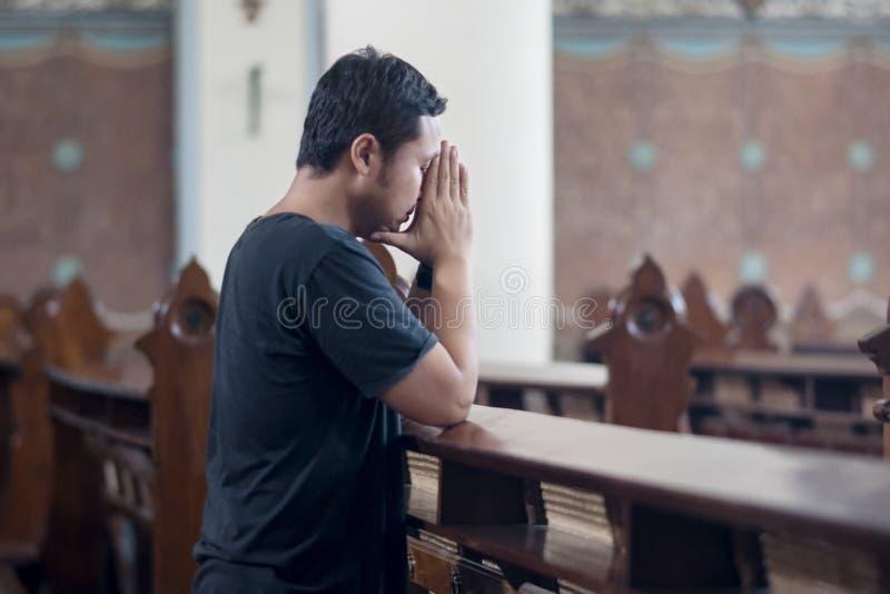 Uomo devoto che prega nella chiesa fotografia stock