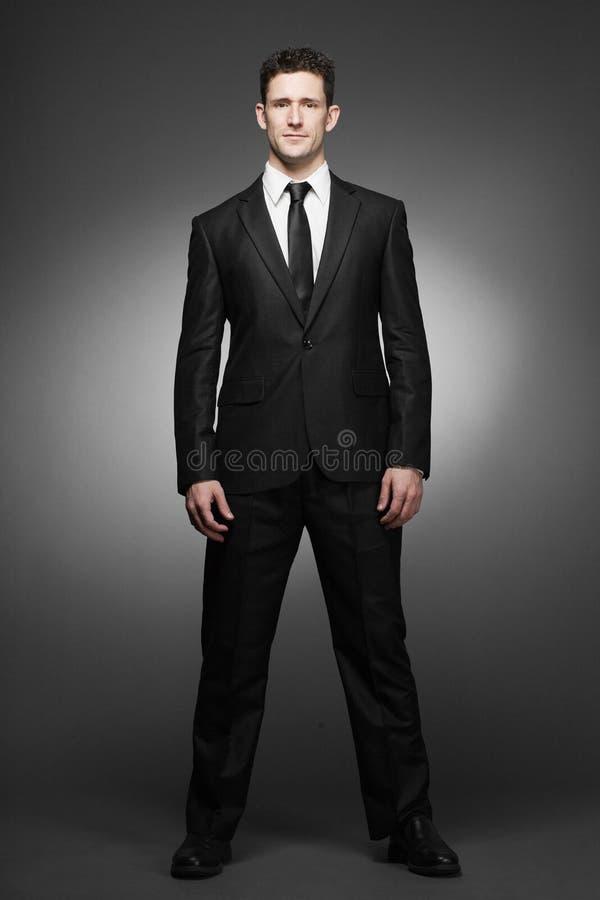 Uomo di affari in camicia bianca ed in vestito nero. fotografia stock libera da diritti