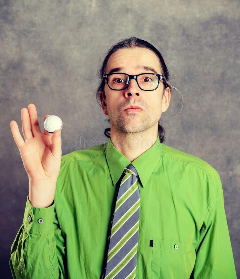 Uomo di affari in camicia e cravatta verdi con palla da golf fotografia stock