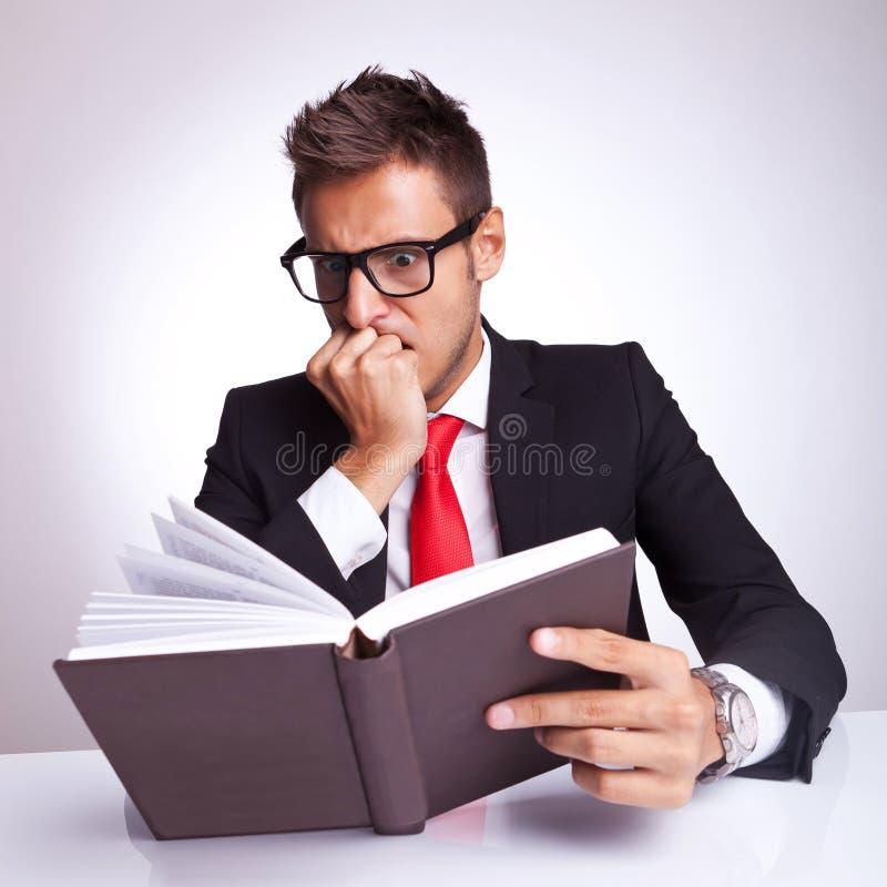 Uomo di affari che è impaurito dal libro fotografie stock libere da diritti