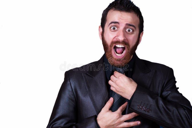 Uomo di affari che afferra il suo legame che grida fotografia stock