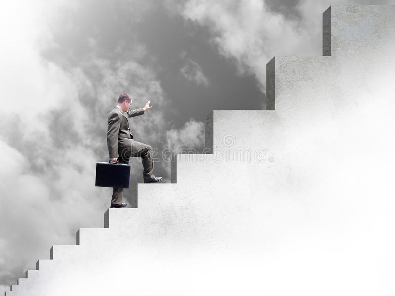 Uomo di affari che arrampica in su le scale al successo fotografia stock