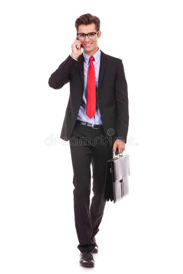 Uomo di affari che cammina e che comunica sul telefono immagini stock libere da diritti