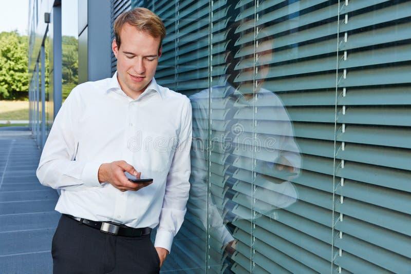 Uomo di affari che chiacchiera con lo smartphone fotografie stock libere da diritti