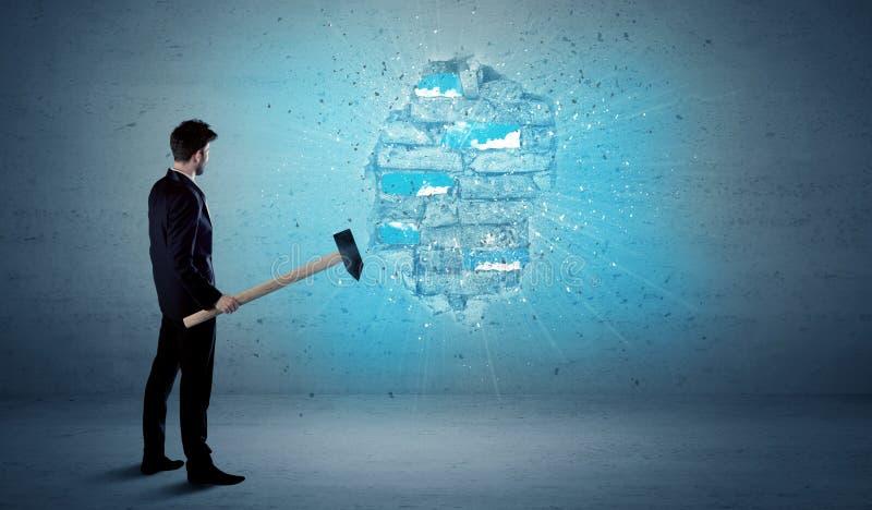 Uomo di affari che colpisce muro di mattoni con il martello enorme fotografie stock libere da diritti