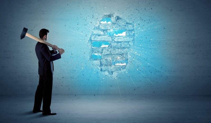 Uomo di affari che colpisce muro di mattoni con il martello enorme immagini stock libere da diritti