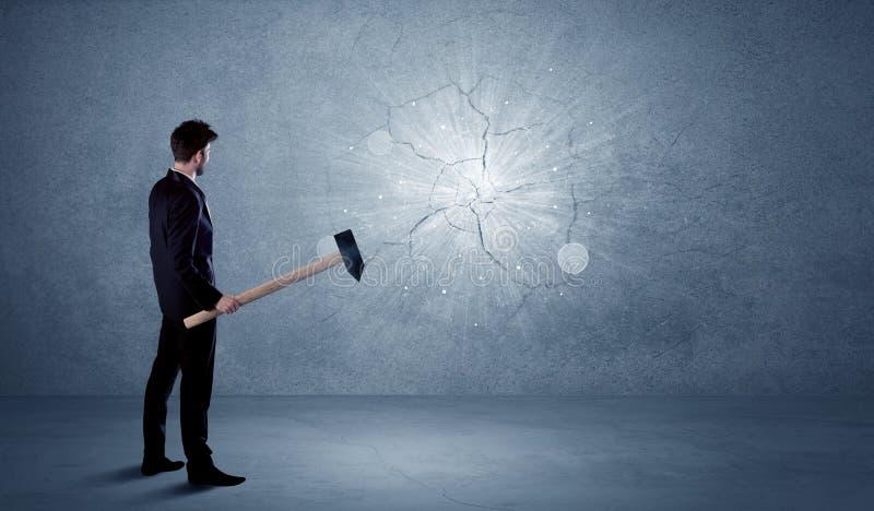 Uomo di affari che colpisce parete con un martello immagine stock libera da diritti