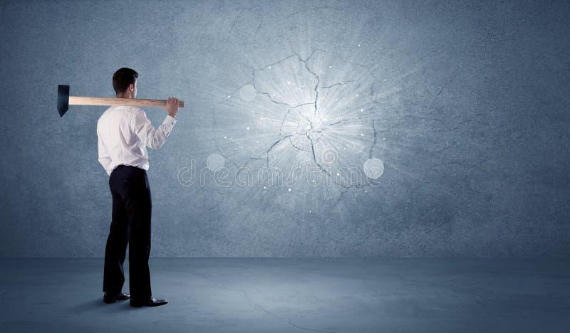 Uomo di affari che colpisce parete con un martello immagine stock