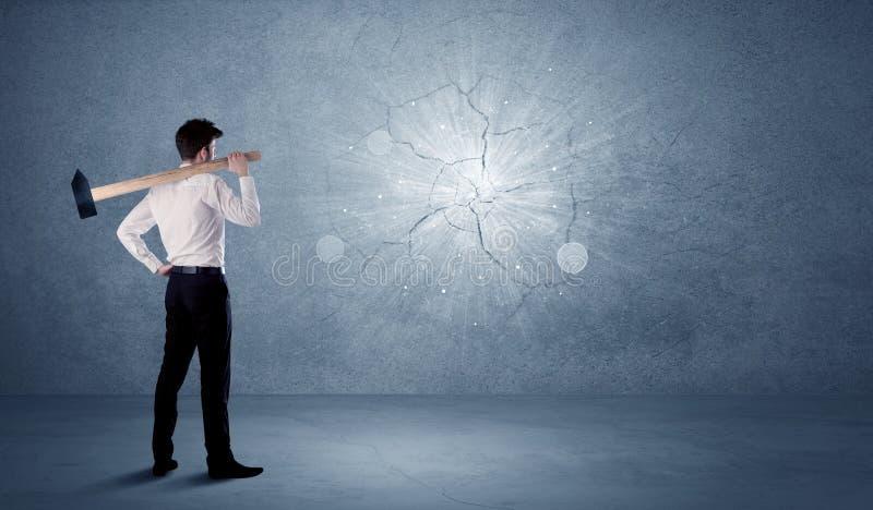 Uomo di affari che colpisce parete con un martello fotografie stock libere da diritti
