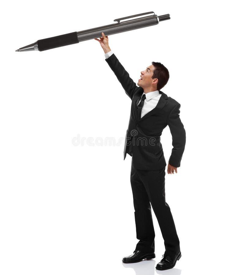 Uomo di affari che consegna una penna enorme fotografie stock libere da diritti