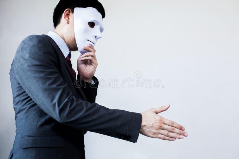Uomo di affari che dà stretta di mano disonesta che si nasconde nella maschera - bus immagine stock libera da diritti