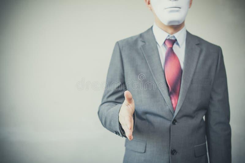 Uomo di affari che dà stretta di mano disonesta che si nasconde nella maschera - frode di affari ed accordo dell'ipocrita fotografie stock libere da diritti