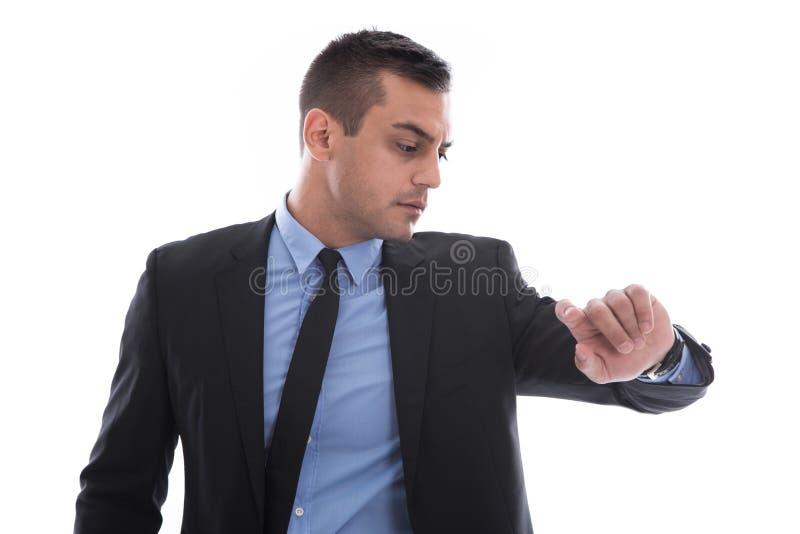 Uomo di affari che esamina il suo orologio. In fretta e furia. Isolato su bianco fotografia stock