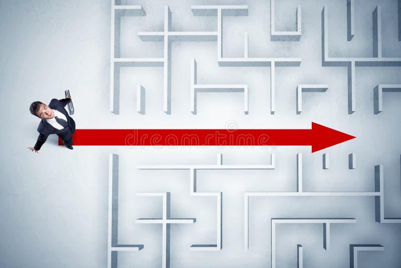 Uomo di affari che esamina labirinto con la freccia rossa immagini stock libere da diritti