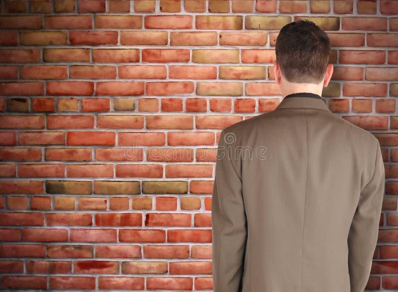 Uomo di affari che esamina ostacolo del muro di mattoni immagini stock libere da diritti