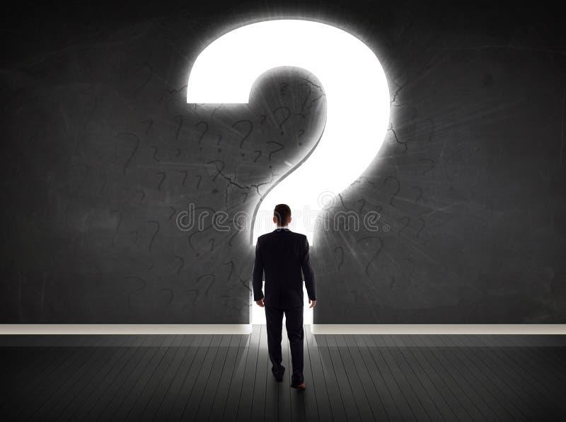Uomo di affari che esamina parete con un punto interrogativo luminoso immagini stock libere da diritti