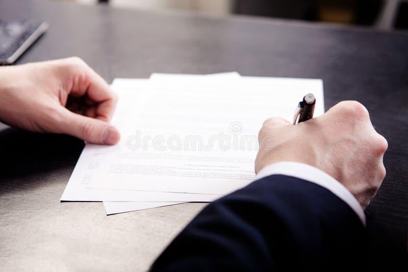 Uomo di affari che firma il contratto - fuoco basso all'atto della stipulazione fotografia stock libera da diritti