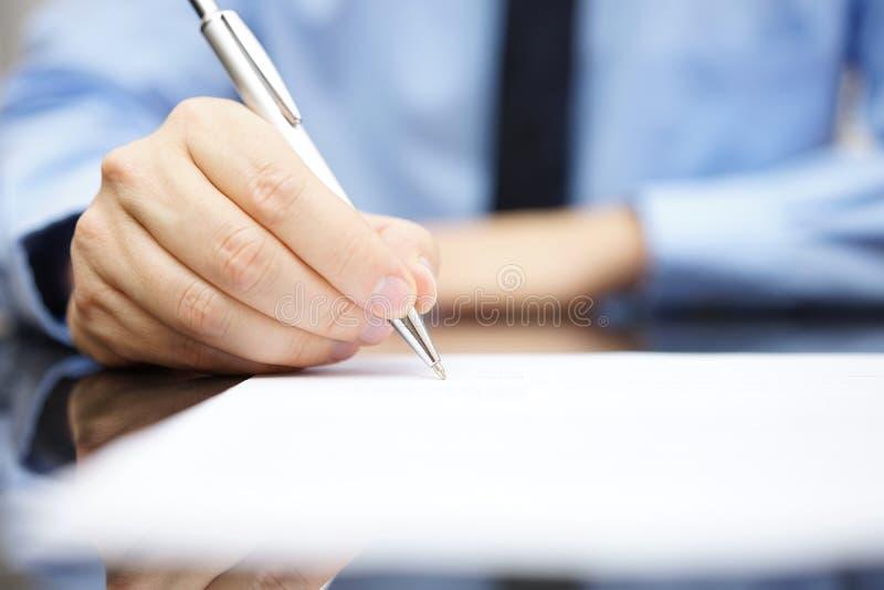 Uomo di affari che firma il contratto per finire un affare fotografia stock libera da diritti