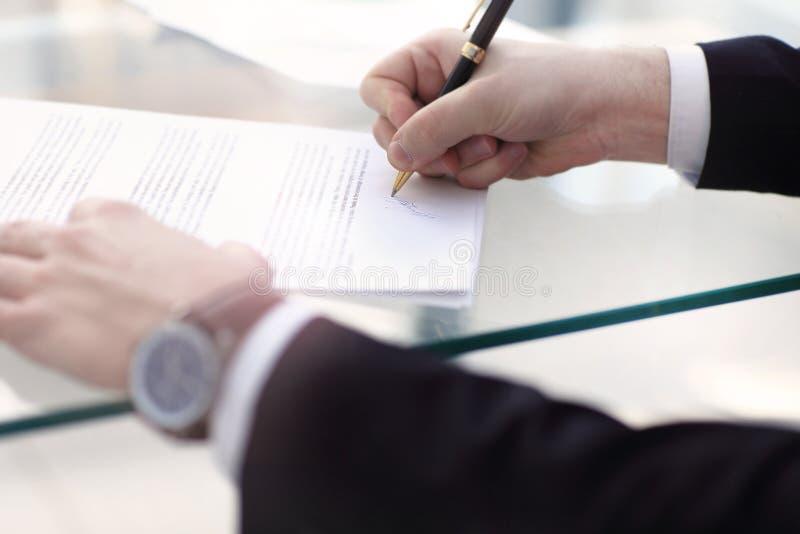 Uomo di affari che firma un contratto fotografie stock libere da diritti