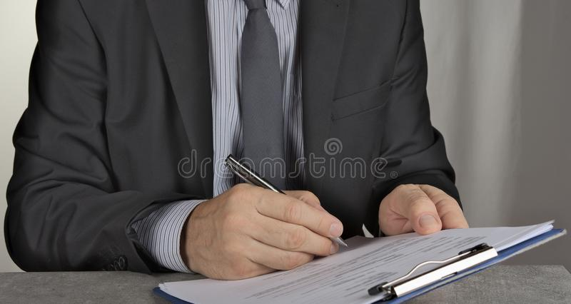 Uomo di affari che firma un contratto che fa un affare, concetto classico di affari fotografia stock libera da diritti