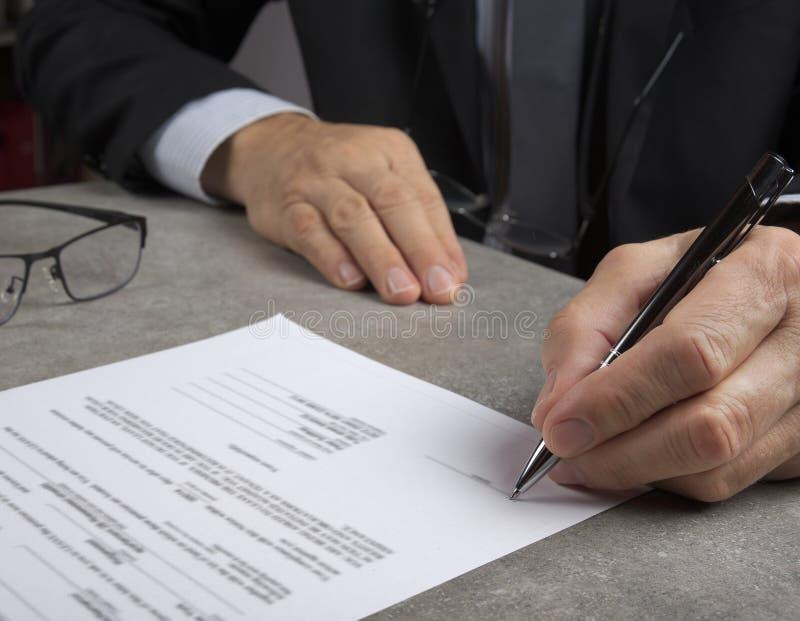 Uomo di affari che firma un contratto che fa un affare, concetto classico di affari fotografia stock