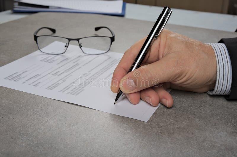 Uomo di affari che firma un contratto che fa un affare, concetto classico di affari immagini stock
