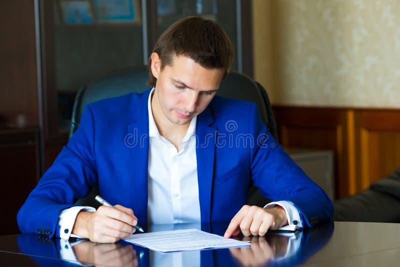 Uomo di affari che firma un contratto in grande ufficio fotografie stock libere da diritti