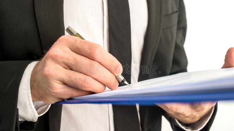 Uomo di affari che firma un contratto o un documento su una mappa immagini stock libere da diritti