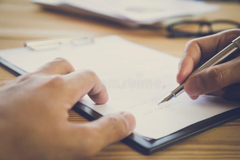 Uomo di affari che firma un contratto Possiede il segno di affari personalmente, direttore della società, procuratore legale Agen immagine stock