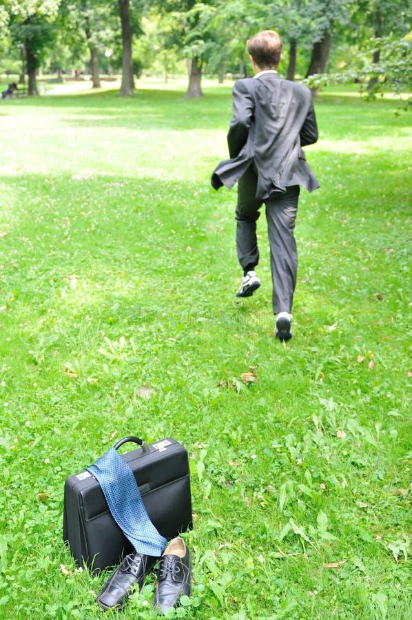 Uomo di affari che funziona nella sosta - fuga fotografia stock