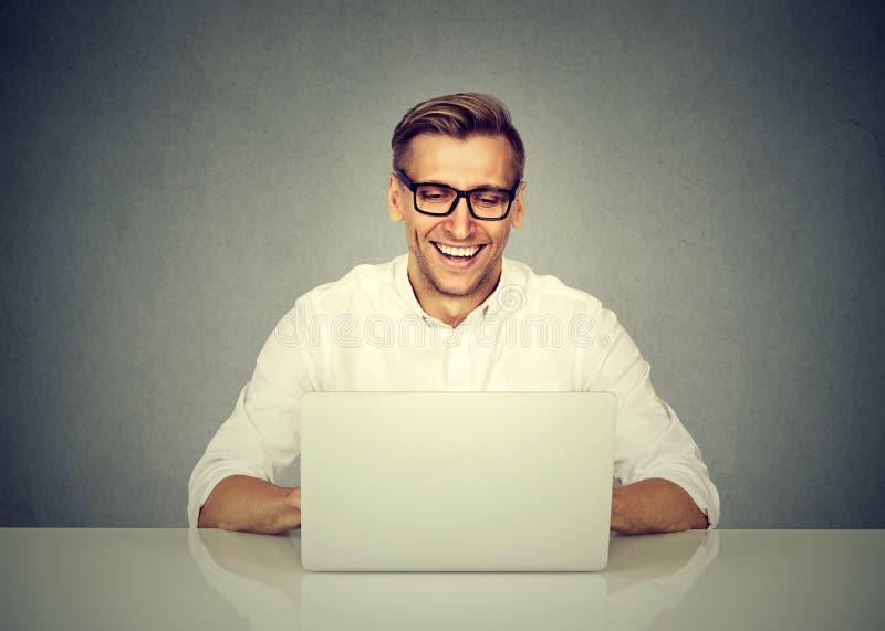 Uomo di affari che lavora al computer portatile, sorridente immagini stock