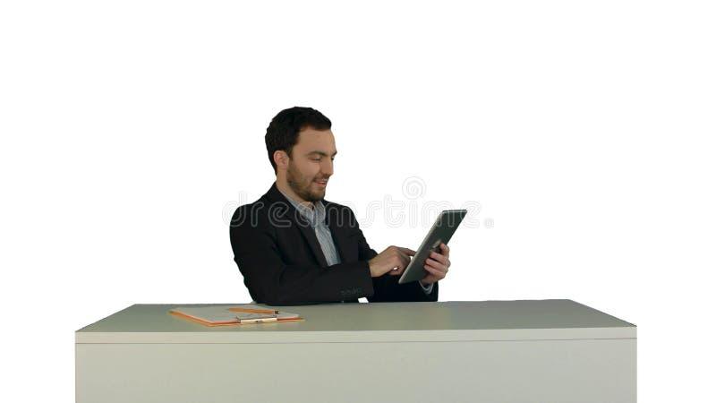 Uomo di affari che lavora alla compressa digitale sulla sua tavola nel suo ufficio su fondo bianco isolato fotografia stock libera da diritti