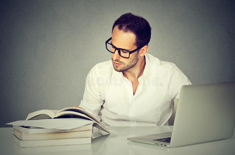 Uomo di affari che lavora con i libri di lettura del computer portatile immagini stock libere da diritti