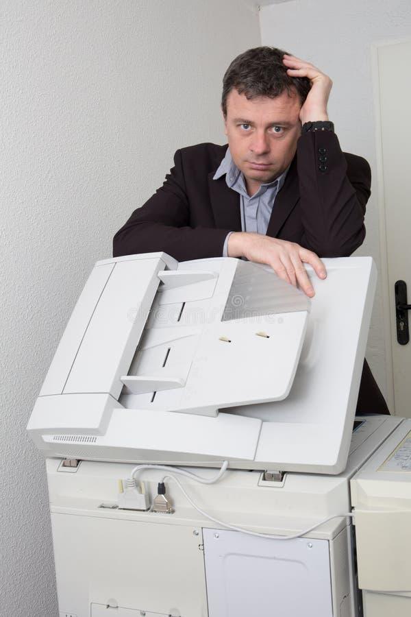 Uomo di affari che lavora davanti alla stampante all'ufficio fotografie stock