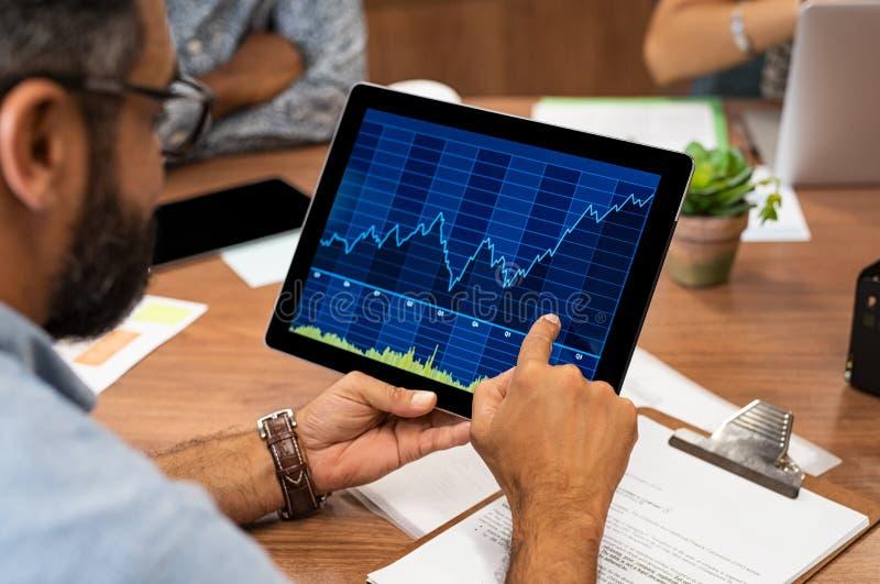 Uomo di affari che legge il grafico del mercato azionario fotografia stock libera da diritti